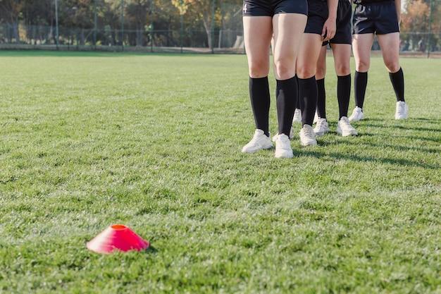 Pernas de mulheres se preparando para correr através de cones Foto gratuita