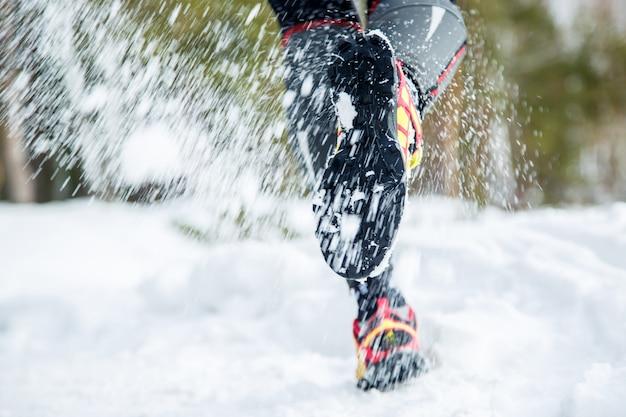 Pernas de um jovem corredor fora na natureza de inverno Foto Premium