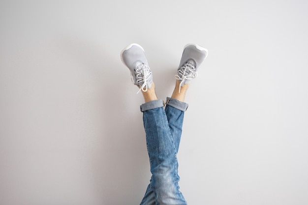 Pernas de um jovem de jeans e tênis em uma parede cinza. Foto Premium