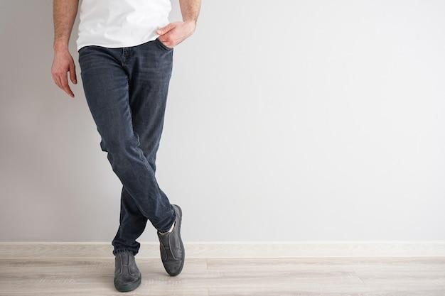 Pernas de um jovem em jeans e tênis em um fundo cinza. Foto Premium