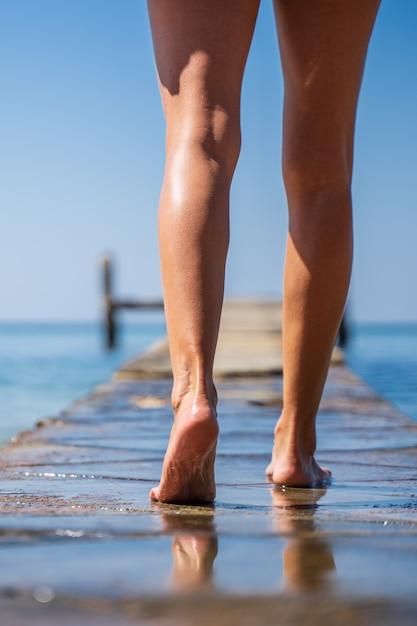 Pernas de uma menina andando em uma ponte de madeira no meio do oceano Foto gratuita