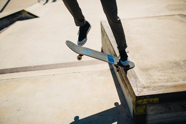 Pernas do patinador durante um truque Foto gratuita
