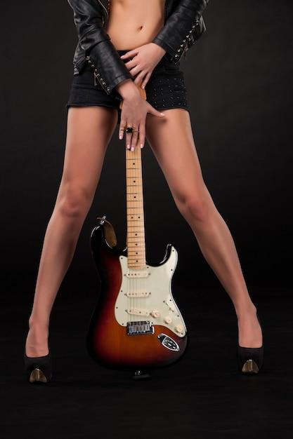 Pernas e mãos da mulher com guitarra elétrica Foto gratuita