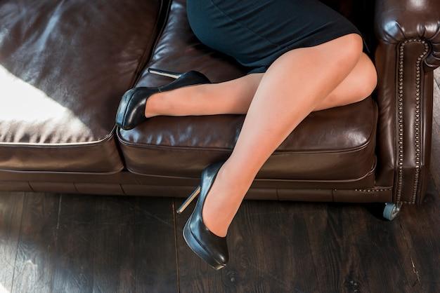 Pernas femininas com sapatos de salto alto preto moda sentado no sofá aconchegante Foto gratuita