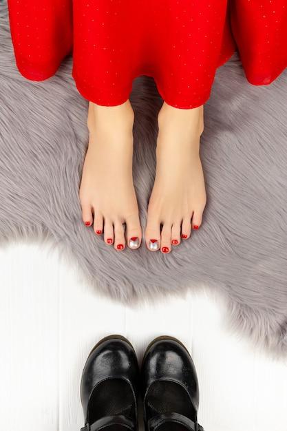 Pernas femininas com unhas vermelhas e sapatos no cobertor fofo cinza. Foto Premium