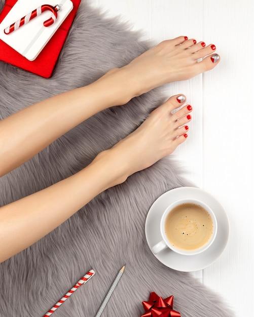 Pernas femininas com unhas vermelhas e xícara de café no cobertor cinza fofo. conceito de celebração de natal. Foto Premium