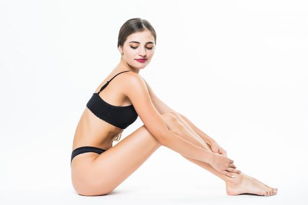 Pernas femininas de mulher bonita jovem isoladas na parede branca Foto gratuita