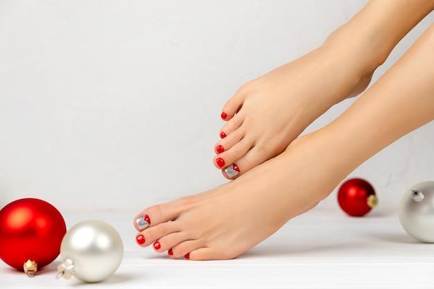 Pernas femininas e enfeites de natal. conceito de salão de beleza de manicure e pedicure. Foto Premium