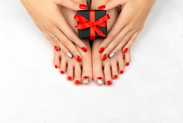 Pernas femininas e hans com unhas vermelhas. conceito de venda de natal. Foto Premium