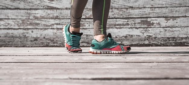 Pernas femininas em meia-calça e calçados esportivos com fundo de madeira, esportes conceituais Foto gratuita