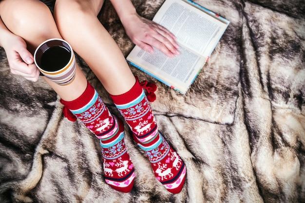 Pernas femininas em meias de natal com um livro e uma xícara de café Foto Premium