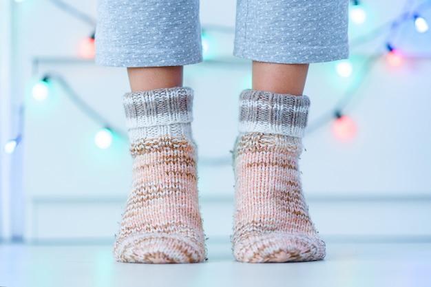 Pernas femininas em meias quentes de malha macias e aconchegantes no inverno em casa. Foto Premium