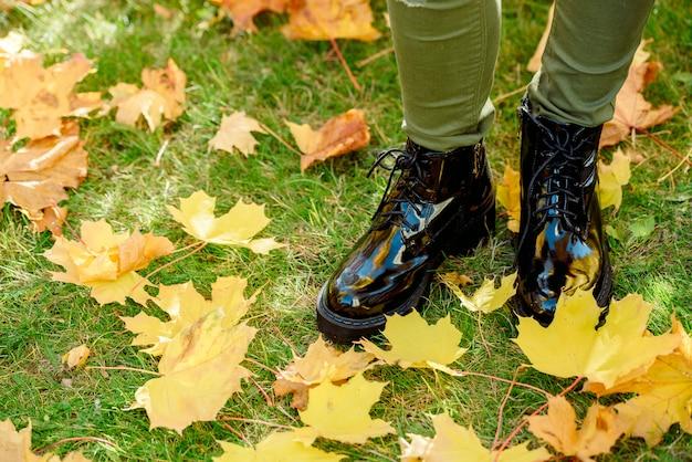 Pernas femininas, em, pretas, couro patente, botas, ficar, ligado, um, tapete, de, amarela, caído, maple sai Foto Premium