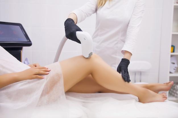 Pernas femininas, mulher na clínica de beleza profissional durante a depilação a laser Foto Premium