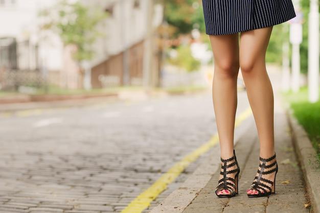 Pernas femininas no antigo pavimento de calçada, vista do chão Foto Premium