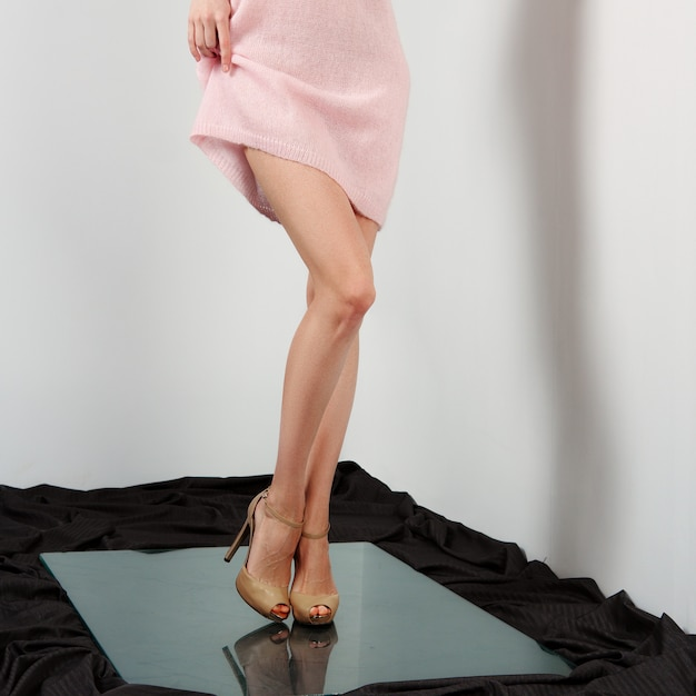 Pernas femininas nuas em sapatos de salto alto. levantando o vestido. Foto Premium