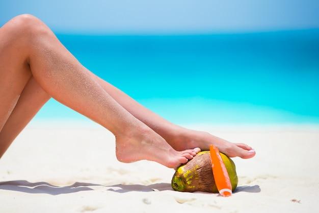 Pernas lisas bronzeadas femininas com suncream e coco na praia branca Foto Premium