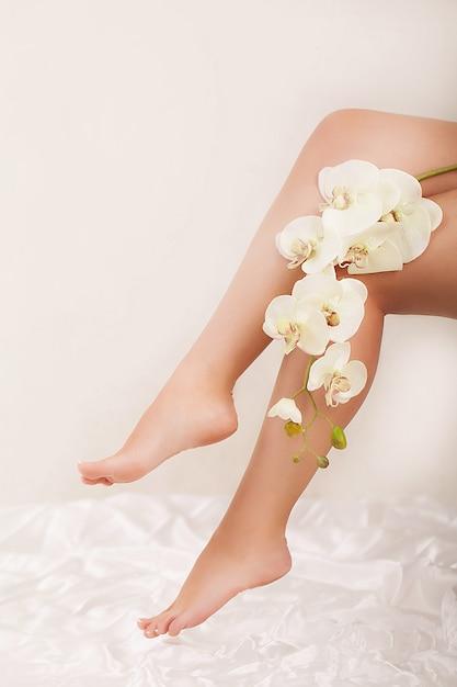 Pernas longas da mulher segurando lindas flores Foto Premium