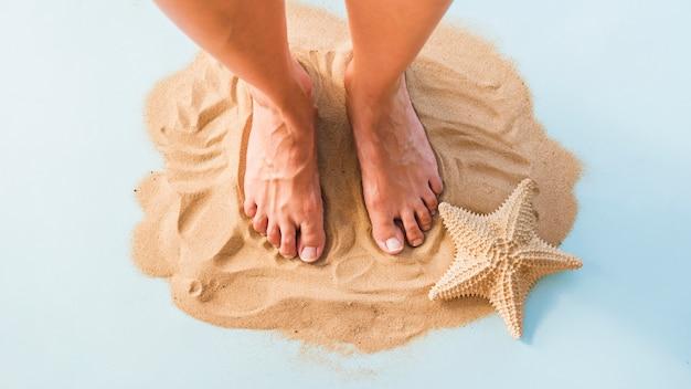 Pernas perto de grande estrela do mar na areia Foto gratuita