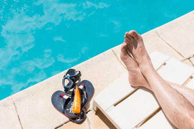 Pernas perto de óculos com loção e flip-flops perto da piscina Foto gratuita