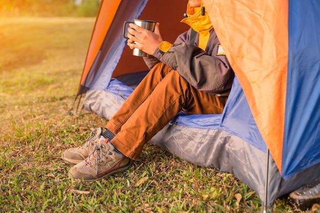 Pernas visíveis da tenda no parque de campismo em fundo de madeira selvagem Foto gratuita