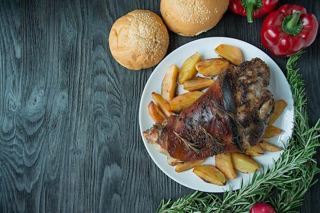 Pernil de porco frito com batatas servido em um prato branco de madeira escura. vista de cima. Foto Premium