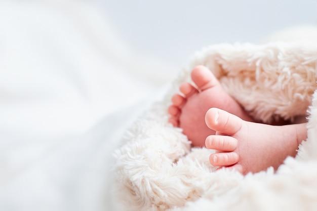 Perninhas de bebê embrulhadas em tecido bege. lugar para texto. cartão infantil. Foto Premium