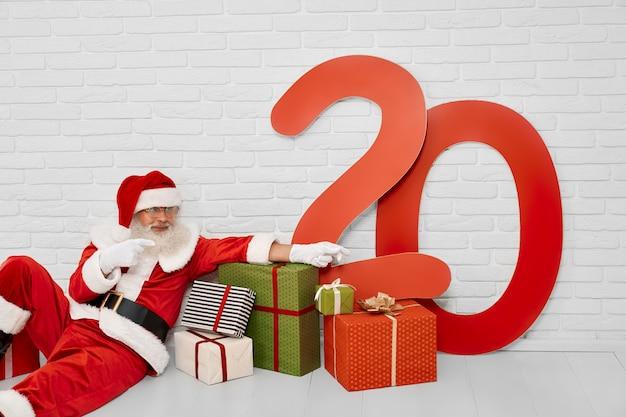 Personagem de natal sênior, sentada no chão com caixas de presente Foto Premium