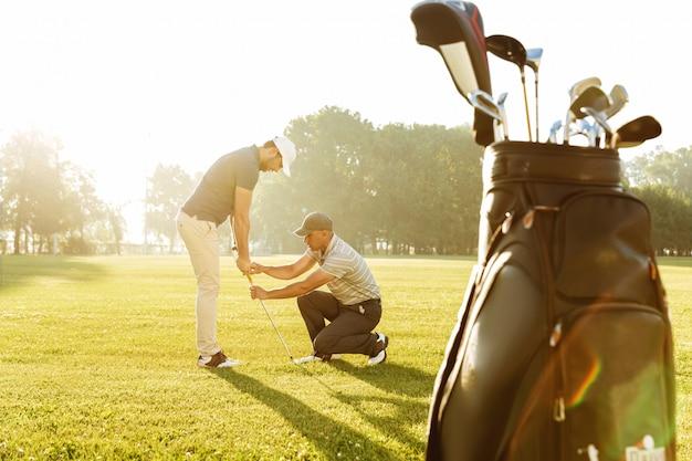 Personal trainer dando uma lição para um jovem jogador de golfe do sexo masculino Foto gratuita