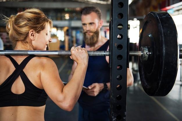 Personal trainer na academia Foto gratuita