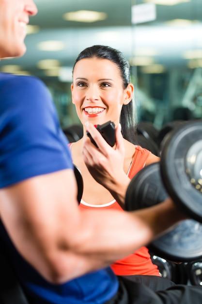 Personal trainer no ginásio e treino com halteres Foto Premium
