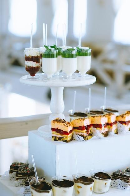 Perto da barra de chocolate do casamento com frutas, biscoitos, bolos, geléia e cupcakes de brilhantes coloridos diferentes. buffet de doces festivos com doces e outras sobremesas. Foto Premium