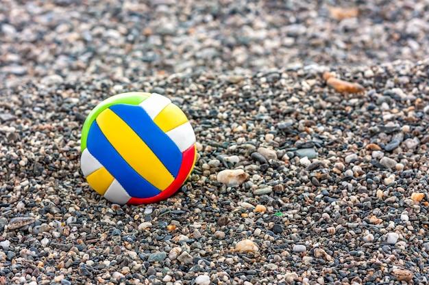 Perto da bola da criança colorida em uma praia de seixos do mar. jogos de verão na praia. Foto Premium