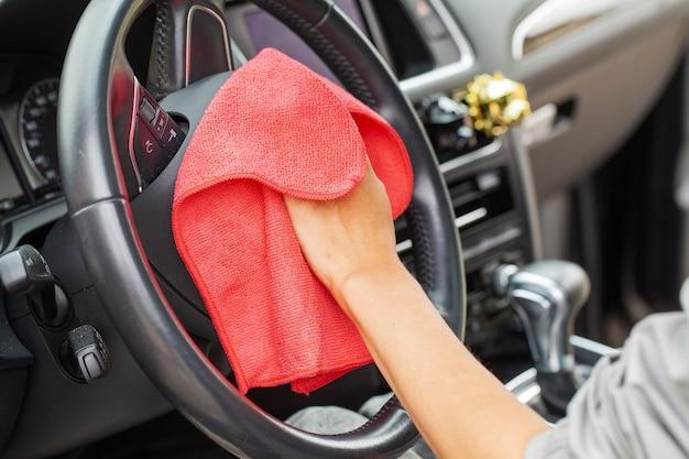 Perto da mulher limpando o interior do carro com um pano vermelho. Foto Premium