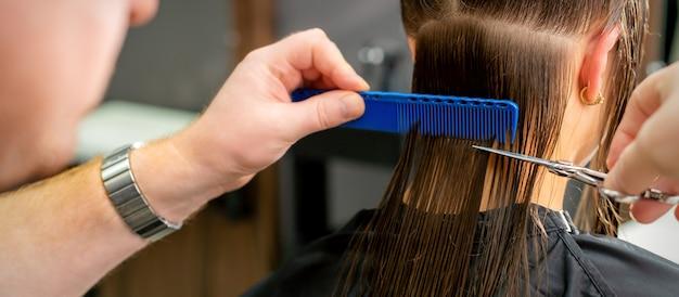 Perto das mãos de um cabeleireiro cortando o cabelo comprido de uma jovem segurando uma tesoura Foto Premium