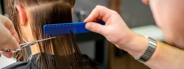Perto das mãos de um cabeleireiro cortando os cabelos longos de uma jovem segurando uma tesoura e um pente no salão Foto Premium