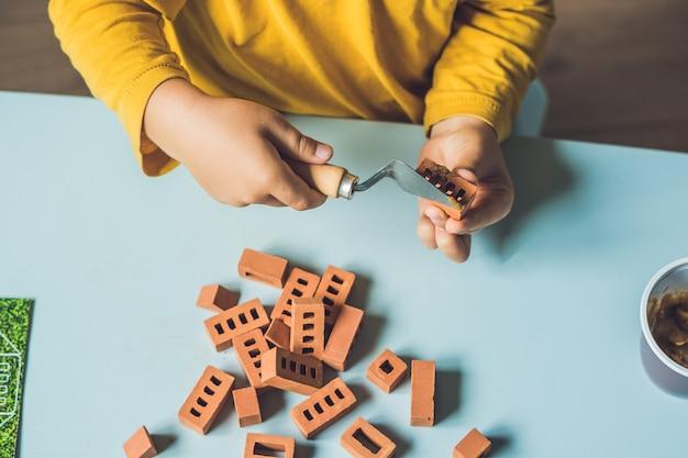 Perto das mãos de uma criança brincando com pequenos tijolos de barro reais na mesa Foto Premium