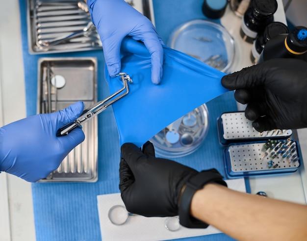 Perto das mãos do dentista usando luvas e segurando instrumentos odontológicos em um fundo azul Foto Premium