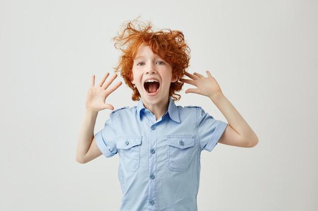 Perto de alegre menino ruivo com sardas pulando e se divertindo Foto gratuita