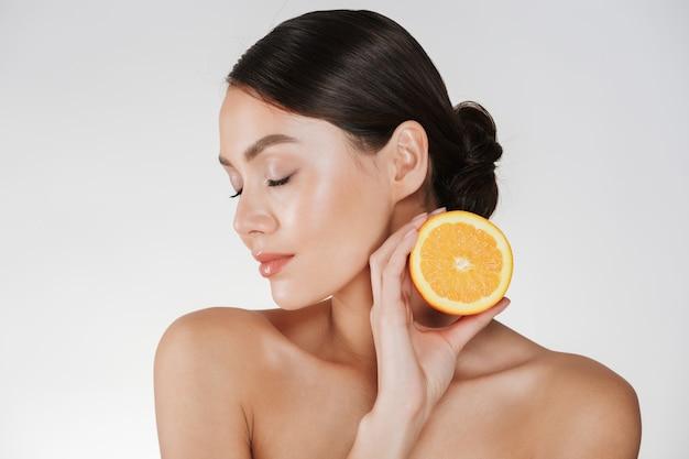 Perto de mulher encantadora, com pele fresca macia, segurando a laranja suculenta, tendo a desintoxicação isolada sobre o branco Foto gratuita
