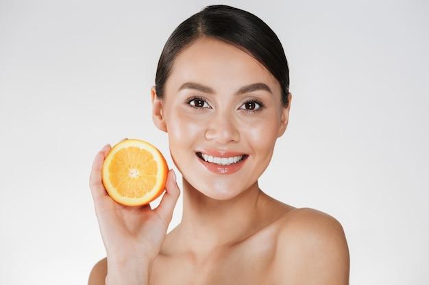 Perto de mulher satisfeita com a pele fresca saudável, segurando a laranja suculenta e sorrindo, isolado sobre o branco Foto gratuita