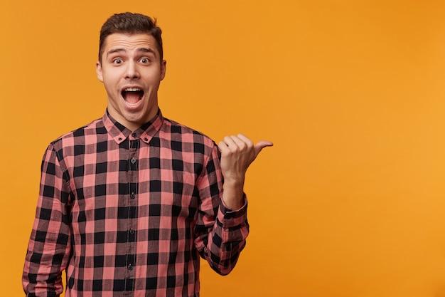 Perto de um homem atraente surpreso e surpreso com uma camisa jeans apontando para o lado direito com o queixo caído Foto gratuita