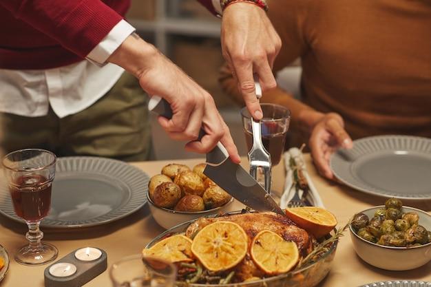 Perto de um homem irreconhecível cortando um delicioso frango assado enquanto desfruta do jantar de ação de graças com amigos e familiares, Foto Premium
