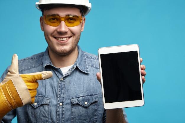 Perto de um jovem mecânico com a barba por fazer bonito, amigável, ou encanador com luvas amarelas Foto gratuita