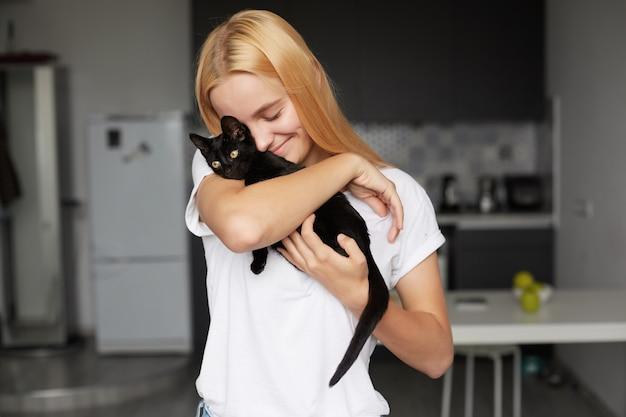 Perto de uma jovem loira na cozinha segurando nas mãos um gatinho preto Foto gratuita