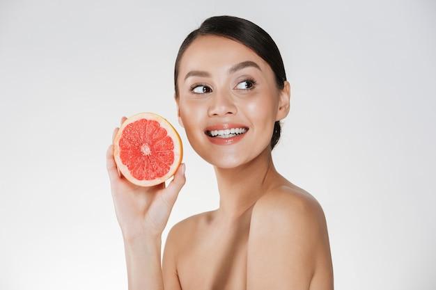 Perto de uma mulher feliz com a pele fresca saudável, segurando a toranja suculenta e olhando de lado com o sorriso, isolado sobre o branco Foto gratuita