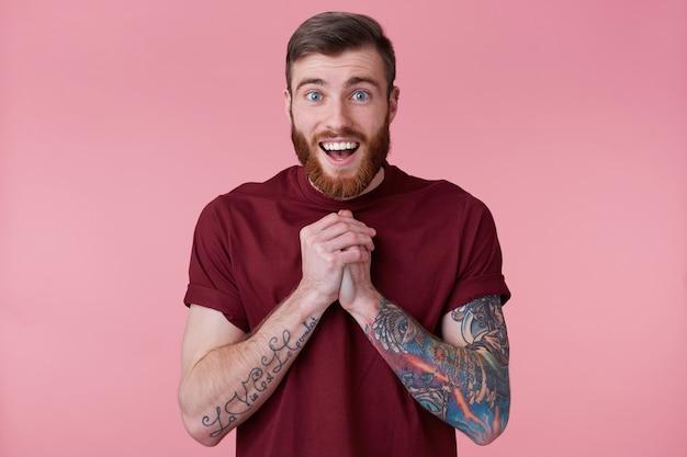 Perto do feliz bonito barbudo jovem com mão tatuada, vi algo fofo e sorridente, olhando para a câmera isolada sobre fundo rosa. Foto gratuita