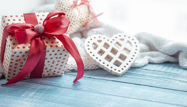 Perto do presente do dia dos namorados e coração decorativo numa superfície de madeira. o conceito de férias de todos os amantes. Foto gratuita