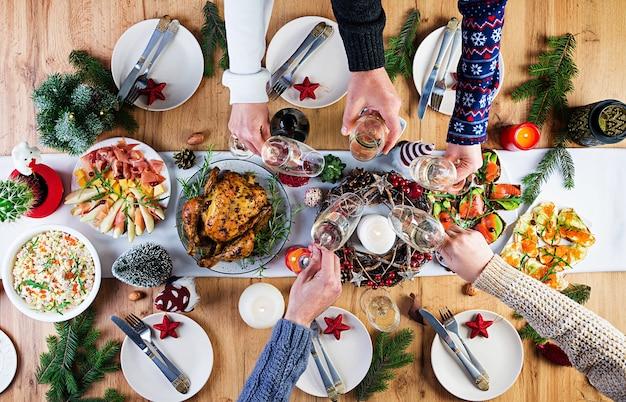 Peru assado. ceia de natal. a mesa de natal é servida com peru, decorada com enfeites brilhantes e velas. frango frito, mesa. jantar em família. vista superior, mãos na moldura Foto gratuita