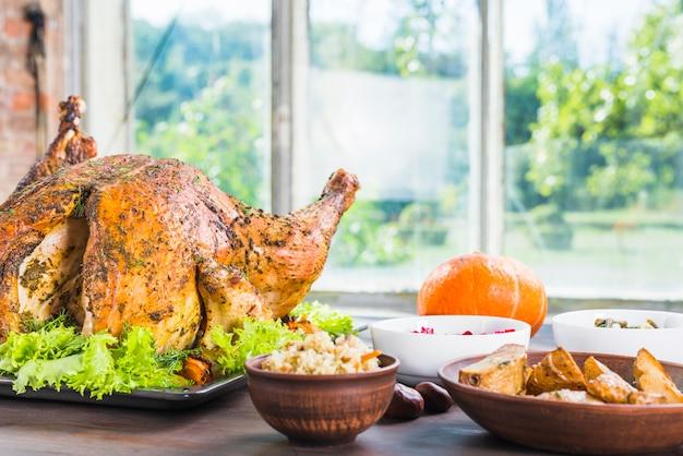 Peru assado com pratos na mesa Foto gratuita